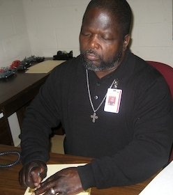 Photo of James Benton reading a Braille book