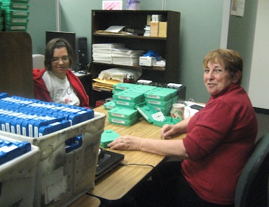 Photo of volunteers Heather McYoung and Bonnie Vaughan inspecting tapes at the Library.