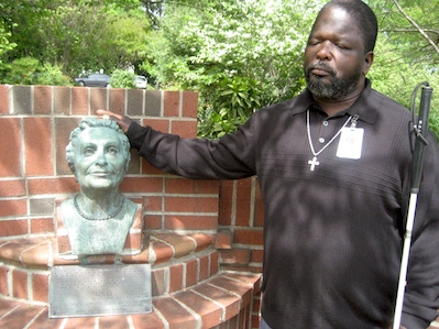 Photo of James Benton by bust of Helen Keller on GMS campus.