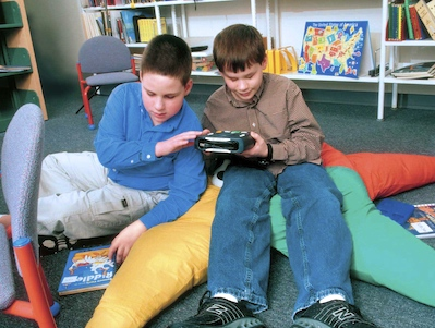 Photo of two young Library patrons examining a playback machine.