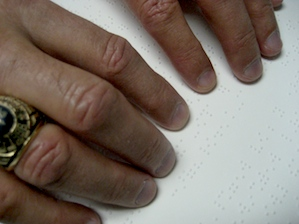 Close-up photo of fingers reading a Braille book.