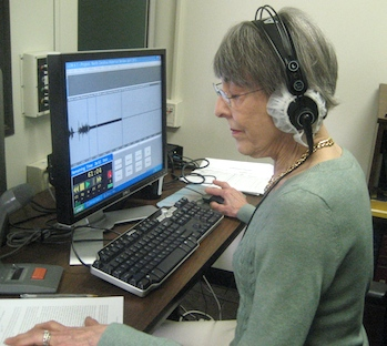 Photo of volunteer Sylvia Perkins outside recording booth at Library.