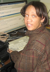 Picture of blind woman using a special computer at the Library to search for a job.